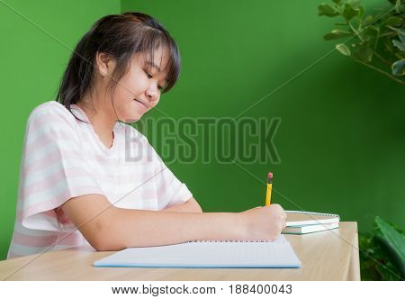 asian young teenager girl writing homework at school library tableeducation concept.
