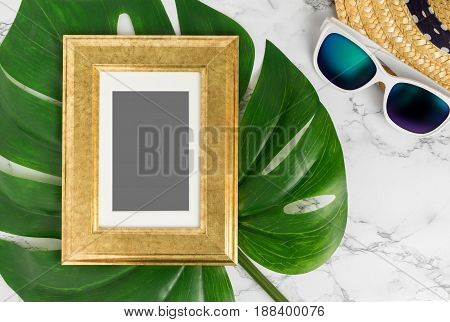 Blank Vintage golden color picture frame on green monstera leaf with sunglasses and straw hat on white marble table top viewMock up for adding your photo in copy spaceSummer vacation.