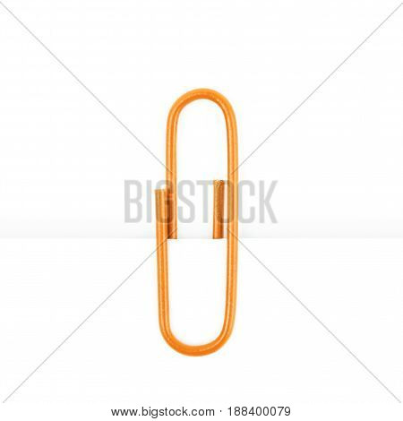 Single office clip attached to a piece of paper, composition isolated over the white background