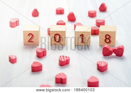 2018 New Year On Wood Cube With Group Of Mini Red Heart On White Rustic Table Top,holiday Concept