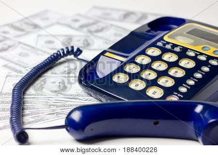 Many American United States 100 dollar bills scattered beside a landline phone on a white background.