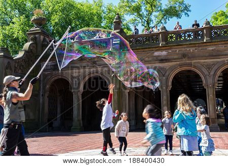 New York NY USA - May 14 2017. Man making soap bubbles for kids near Bethesda Fountain in Central Park