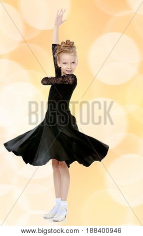 The slender little blonde girl dancer in the long dress of black color made specifically for performing .Girl stands sideways to the camera and raised his hand up.