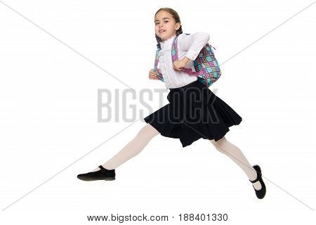 Beautiful little blond schoolgirl, with long neatly braided pigtails. In a white blouse and a long dark skirt.She jumps over the obstacle.Isolated on white background.