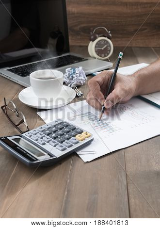 business person analyzing graphs and taking notes with hot coffee and calculator