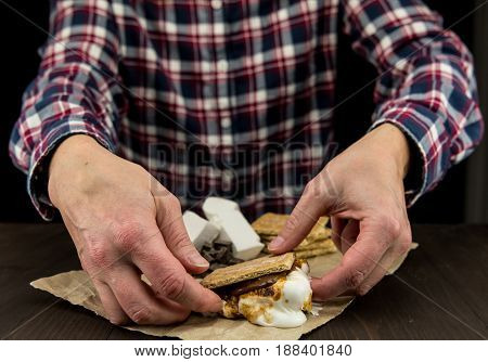 Womans Hands Reach Out to Pick up a Smore with oozing marshmallows