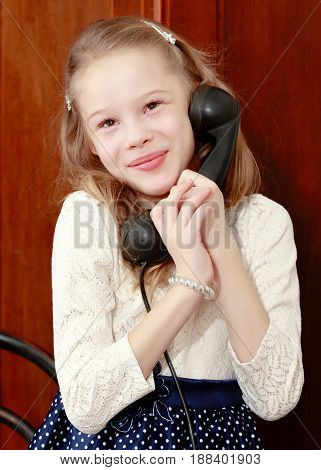 Cheerful little girl talking on a vintage telephone in the interior of the sixties of the last century.Retro style.