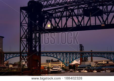 The rising full moon shines through a railroad lift bridge over the Cuyahoga River in Cleveland Ohio
