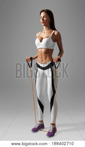 EMS fitness woman doing cross fit training exercises for hands and back with expander. Isolated on gray background with clipping path.