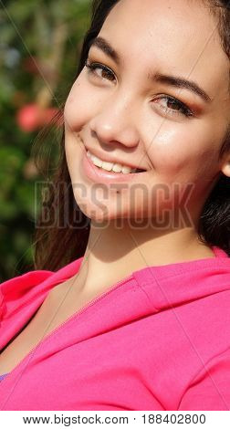 Hispanic Girl Smiling Wearing a Pink Sweatshirt