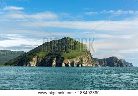 Rocks with caves and grottoes in Avacha Bay of the Pacific Ocean. The coast of Kamchatka.