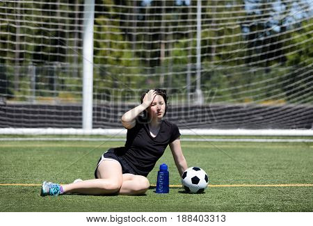Teen age holding her head while resting on the soccer field during a hot day