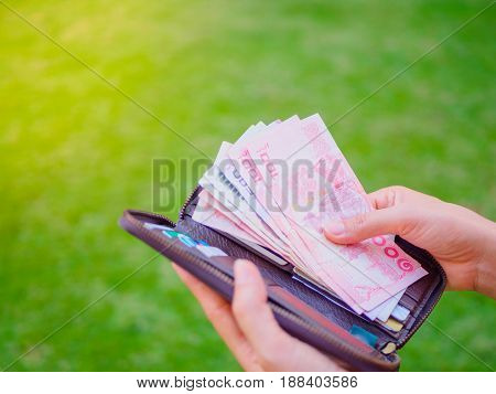 Women Hands taking out money thai baht from wallet on the green grass field