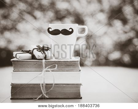 Father's day concept. Black and white of stack of books gifts tea cup with black Mustache and flower on background