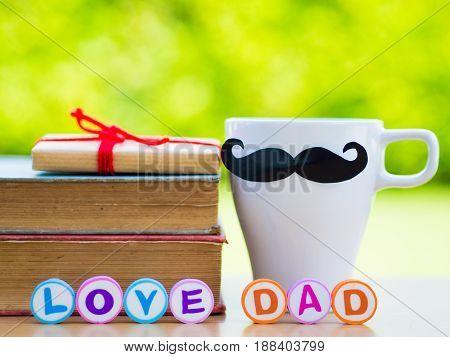 Father's day concept. LOVE DAD alphabet on stack of books gifts tea cup with black Mustache and flower on background