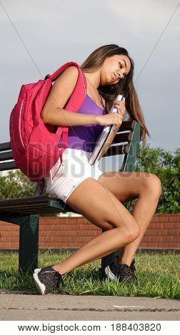 Youthful Girl Student Sitting on a Park Bench