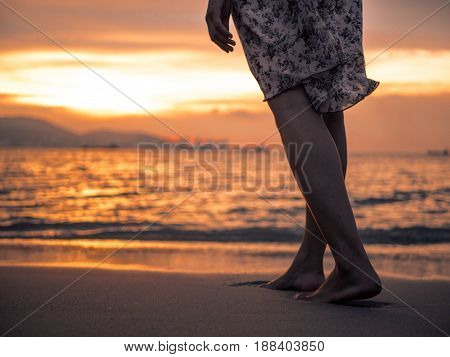 silhouette of Young woman walking alone on the beach in the sunset
