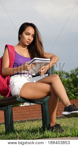 Pretty Female Student Sitting on a Park Bench