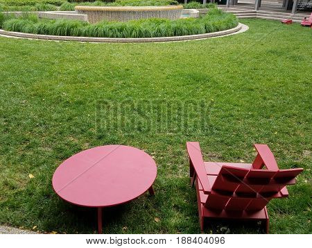 red chairs and table on green grass and water fountain