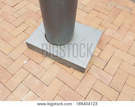 black metal pole and red brick sidewalk
