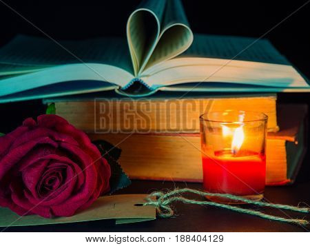 Low key of Valentines Day background-red rose with red candle and open book in heart shape on stack of books.