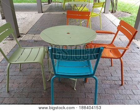 green table with brightly colored chairs outdoors