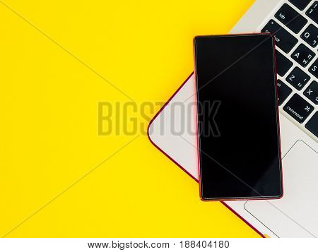 Top view of smartphone on laptop on yellow background