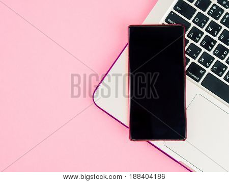 Top view of smartphone on laptop on pink background