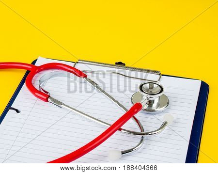 Stethoscope with clipboard on yellow background for Doctor working in hospital writing a prescription Healthcare and medical concept