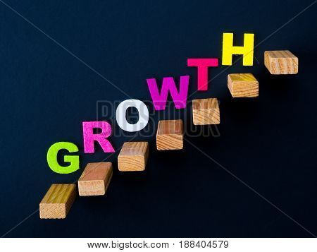 "Wood block stacking as step stair with colorful of ""GROWTH"" word on it in black background. Business concept for success process."