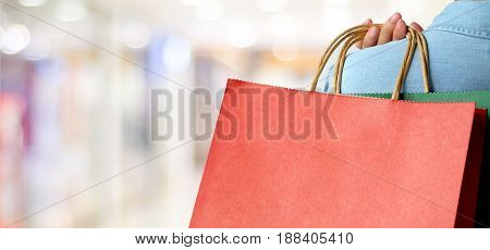 Hand holding red shopping bag on blur store background banner with copy space for text template business concept