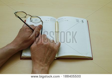 A hand with glasses lies on a pad. Making a decision