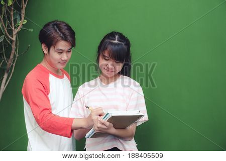 Young man and girl writing on notebook paper while standing in front of green wall background education background banner