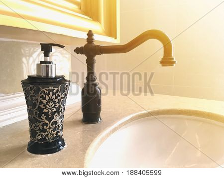 Black vintage water tap and bottle of liquid soap in bathroom