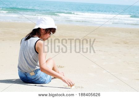 Asia girl sitting on beach background in summer holiday vacation