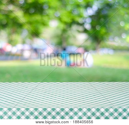 Empty table with green tablecloth over blur park with people and bokeh background food and product display montage