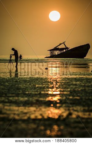 photographer taking a photography of abandon wreck boat in phuket southern thailand
