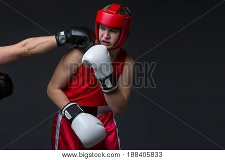 Teenage boxer in red form and helmet is being punched into face. Studio shot on black background. Copy space.