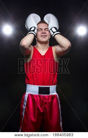 Disappointed teenage boxer in red form and white gloves, backlights. Studio shot on black background. Copy space.