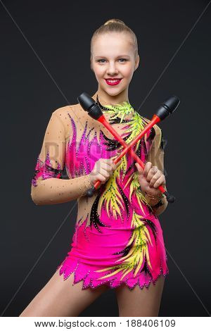 beautiful blond teen age gymnast girl making exercises with maces. Studio shot ion black background. Copy space.