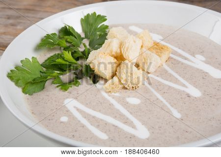 Creamy mushroom soup with croutons and parsley