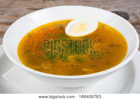 Russian soup with egg served in a bowl on a wooden table