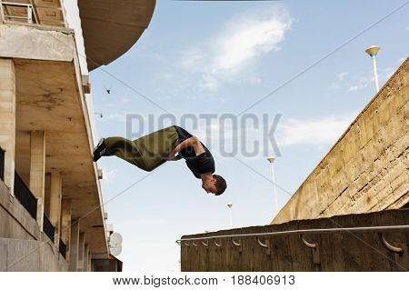 Young man back flip. Parkour in the urban space. Sport in the city. Sport Activities outdoors.