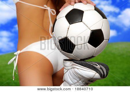 Girl in bikini with soccer ball on juicy green field