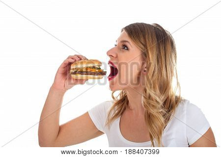 Picture of a pretty young woman eating a delicious hamburger posing on isolated background