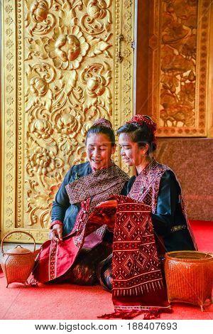 NAKORN PHANOM THAILAND - FEBRUARY 14 2015: Tourist senior ladies visit and join Thai northeastern Phutai world event day looking to local woven fabric in Buddhist church in Renunakorn of Nakorn Phanom Thailand