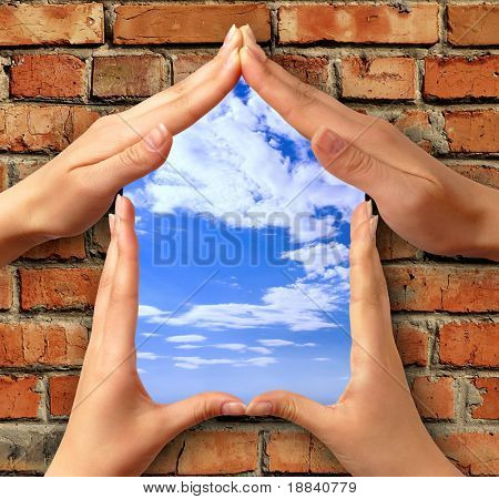 Home symbol made from hands over a brick with a window into blue sky conceptual photo illustration