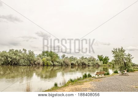Peaceful stretch of a river with benches for relaxing and enjoying the quiet