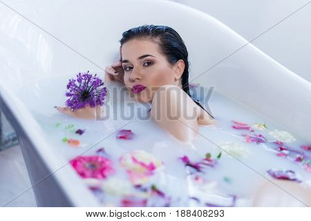Sexy brunette woman lying on one side in a hot bath with flowers. she is wearing black sexual lingerie. woman in bath