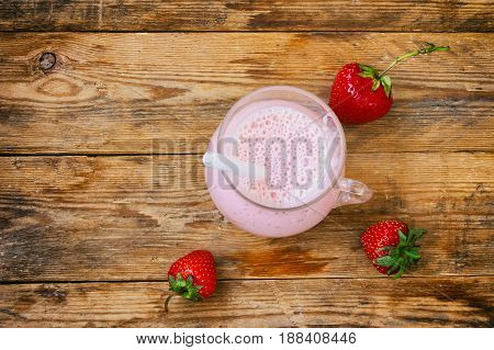 Strawberry milkshake in a glass three berries on a wooden table rustic style